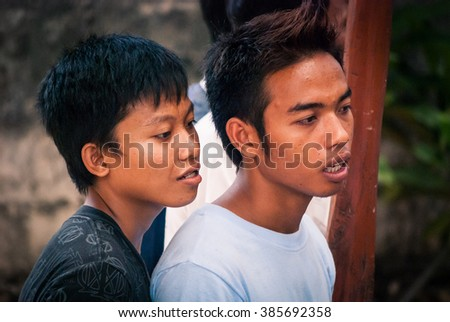LEMBONGAN, BALI, INDONESIA - MAY 10, 2010: Two young spectators of a cockfighting match anxiously following the events in the ring. Cockfights are very popular events among Balinese men.