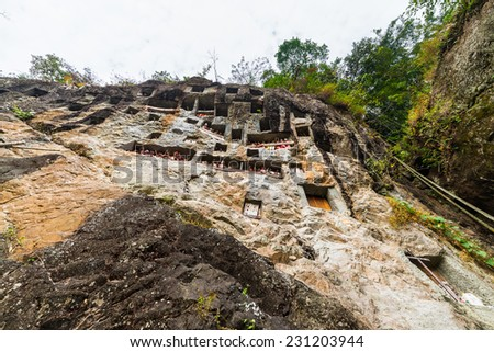 Lemo (Tana Toraja, South Sulawesi, Indonesia), famous burial site with coffins placed in caves carved into the rock, guarded by balconies of dressed wooden statues, images of the dead persons. - stock photo