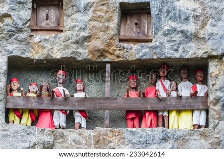 Lemo (Tana Toraja, South Sulawesi, Indonesia), traditional burial site with coffins placed in caves guarded by balconies of dressed wooden statues, images of the dead persons (tau tau). - stock photo