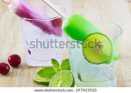 lemon and cherry popsicles on ice glass wooden background, soft focus - stock photo