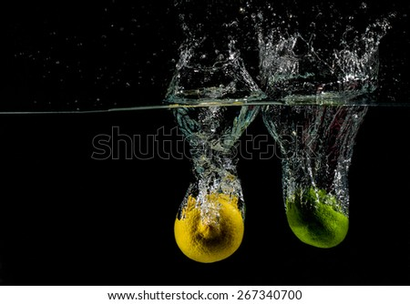 Lemon and lime create splash in water with dark background. - stock photo