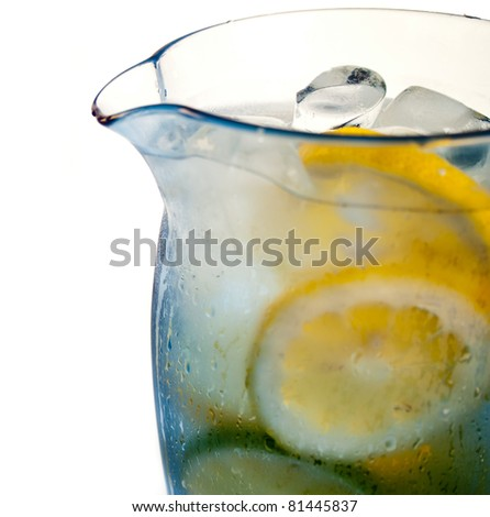 lemon and lime floating in cold water in a blue pitcher - stock photo