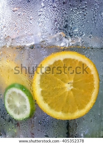 Lemon and lime in the iced water bucket for summer. Only the water drops on the glass are in focus while the content inside is blurred to make the overall picture look cold and refreshing. - stock photo