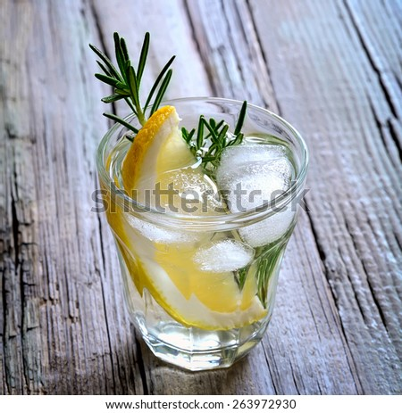 Lemon and rosemary soda with ice cubes in a glass or maybe refreshing summer alcoholic cocktail - stock photo