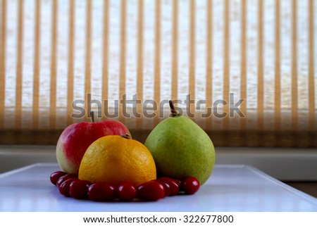 Lemon, apple, pear and dogwood berries on white tray at kitchen