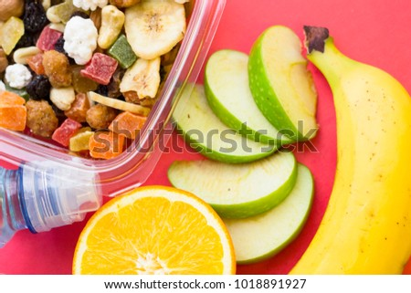 Lemon, banana, slices of green apple and a plastic container of candied fruit, top view, close up, rose background