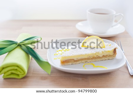 lemon cake on a white porcelain plate, dessert fork and a napkin tied with a bow green in the background with a cup of tea, wooden table