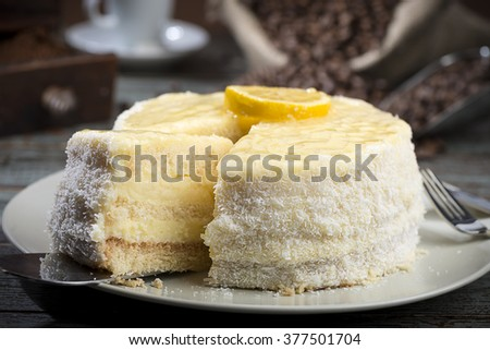 Lemon cake with coffee mug at the background, on table.
