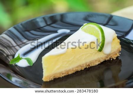 Lemon cheese cake on a black plate. - stock photo