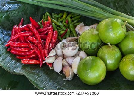lemon, chili peppers, Garlic, Green onion - stock photo