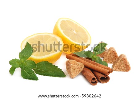 Lemon citrus with mint leaves, heart-shaped cane sugar and cinnamon sticks on white background - stock photo
