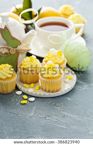 Lemon cupcakes for Easter brunch with yellow frosting and sprinkles - stock photo