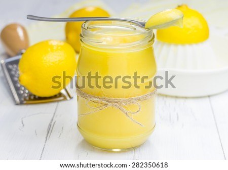 Lemon curd in a glass jar with fresh lemons on background - stock photo