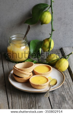 Lemon curd tarts and baked pastry on a plate and a jar of lemon curd and fresh lemon on background - stock photo