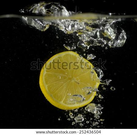 lemon drop in water (black background) - stock photo