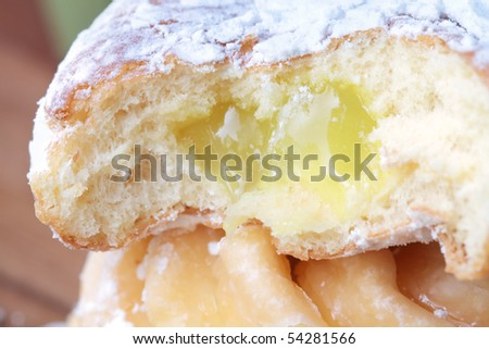 Lemon filled jelly donut stacked on another donut. Shallow DOF.