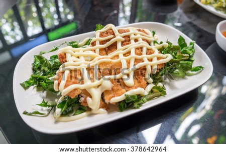 Lemon fried chicken topped with mayonnaise decorate white plate and vegetable fried - stock photo