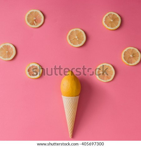 Lemon fruit in ice cream cone with lemon slices on pink background. Minimal concept. Flat lay. - stock photo
