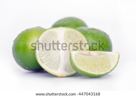 Lemon fruit (Other names are lime in French, citrus fruit, lime green, Key lime, Persian lime, Kaffir lime, desert lime) with half cross section and partial section isolated on wooden board - stock photo