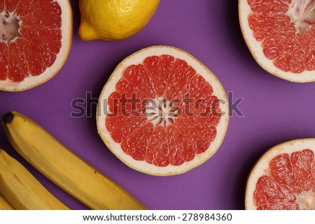 Lemon, grapefruits and bananas on bright lilac background