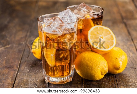 lemon ice tea on brown wooden table with lemons around - stock photo