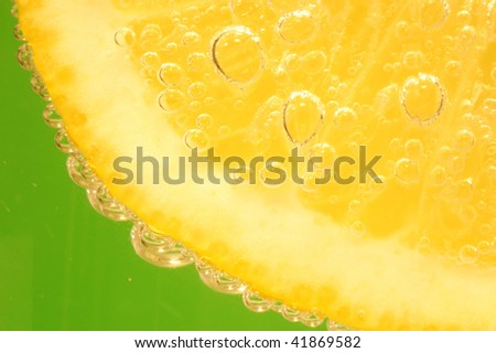 Lemon in soda water with green background