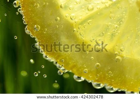 lemon in sparkle water background with sparkle water drops on glass for background or backdrop. Sparkle water background. Natural green water background. Fresh lemon juice concept. - stock photo
