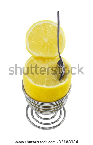 Lemon in the metal spiral eggcup with spoon on the white background