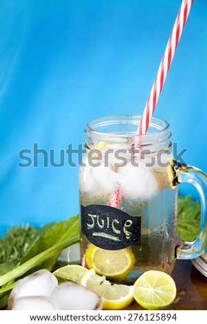 lemon juice with red straw on blue background - stock photo