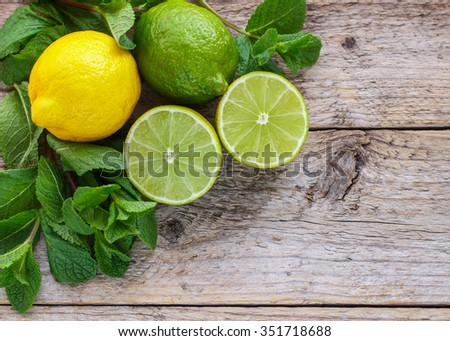 Lemon, lime and mint - juicy ripe citrus on an old wooden table. The ingredients to make a Mojito cocktail - stock photo