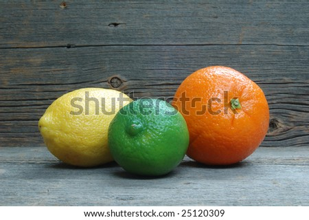 Lemon, lime and orange on distressed old barnwood - stock photo