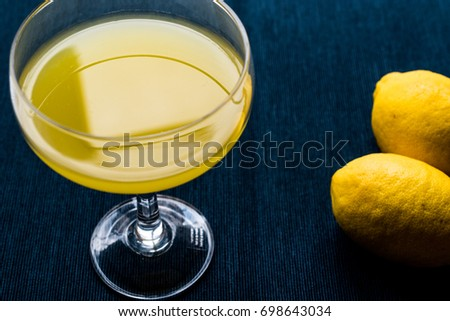 Lemon Liqueur Limoncello with lemon on white wooden surface.