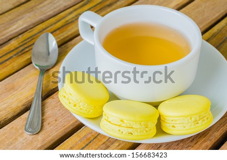 Lemon macaroon on wood table with white tea cup
