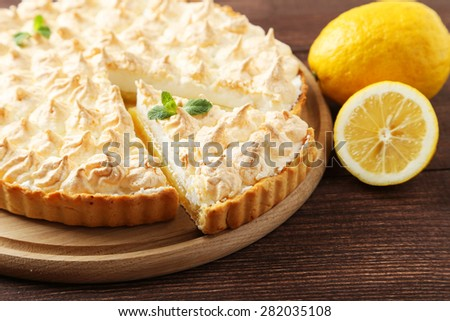 Lemon meringue pie on cutting board on brown wooden background - stock photo