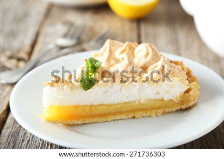 Lemon meringue pie on plate on grey wooden background