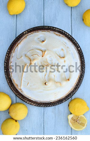 Lemon Meringue Pie with fresh lemons over a beautiful blue wooden background.