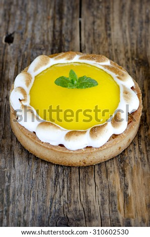 Lemon meringue tart on a wooden board