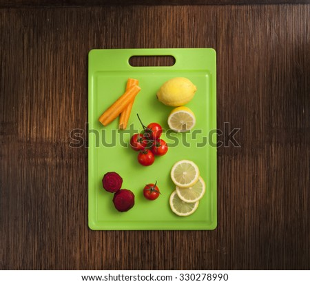 lemon , mini tomatoes carrot and beetroot on green plastic cutting surface on wooden background - stock photo