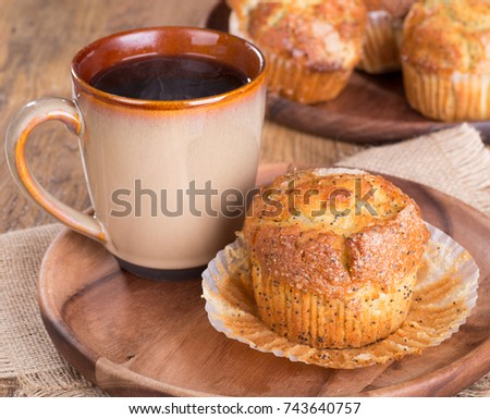 Lemon poppy seed muffin and cup of coffee on a wooden plate