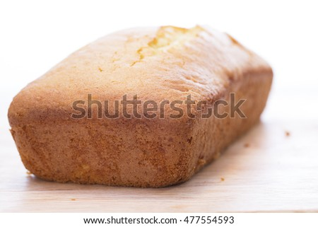 Lemon pound cake loaf uncut on cutting board.