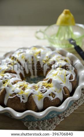 Lemon pound cake with frosting and a lemon zest garnish.
