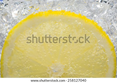Lemon Slice in Fizzy Water Bubble Background with ice cube - stock photo