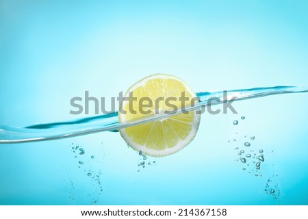 Lemon Slice in water on turquoise background - stock photo