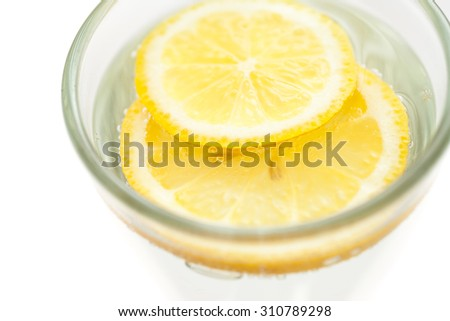 Lemon slices in sparkling water glass, minimalist healthy drink - stock photo