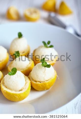 Lemon sorbet or ice cream inside fresh lemons decorated with mint leaves on big white plate - stock photo