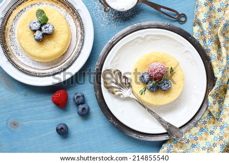 Lemon Surprise Pudding cake served with berries on plate - stock photo