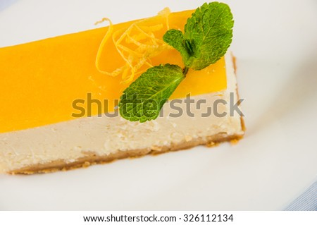 Lemon tart on a plate with fresh mint leaf.