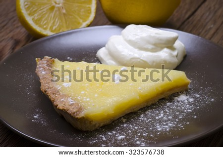 Lemon tart with creme fraiche and powdered sugar - stock photo