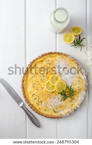 Lemon tart with rosemary, sweet quiche, milk and fresh herbs from garden - stock photo