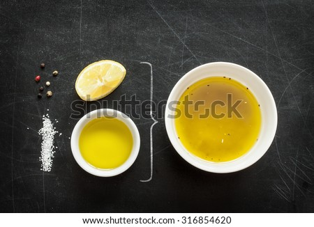 Lemon vinaigrette dressing - recipe ingredients on black chalkboard background from above. Lemon, olive oil, salt and pepper. Layout with free text space. - stock photo